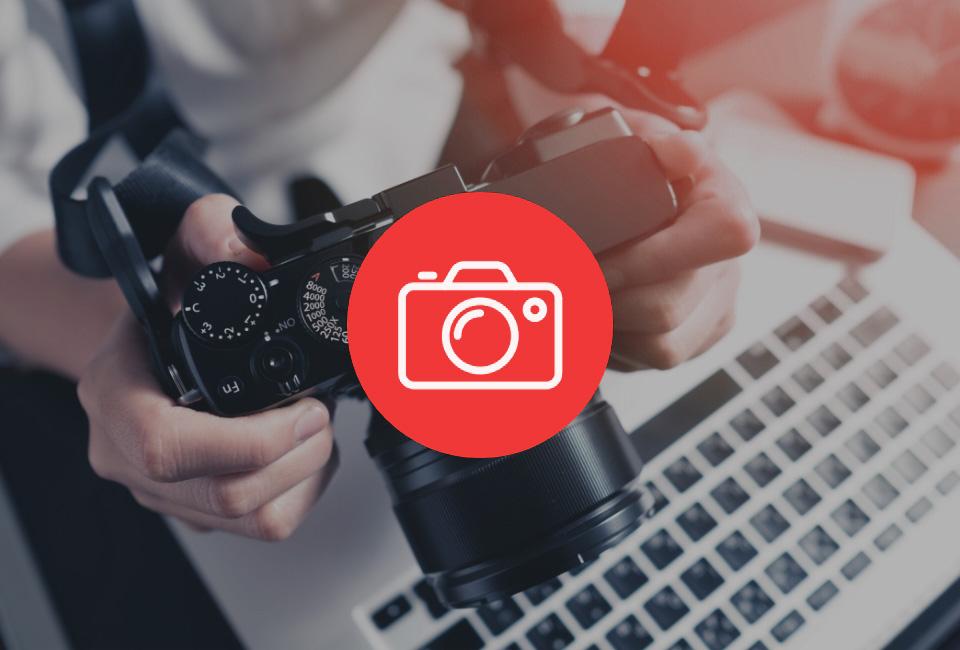 Osoba trzyma aparat fotograficzny wdłoniach