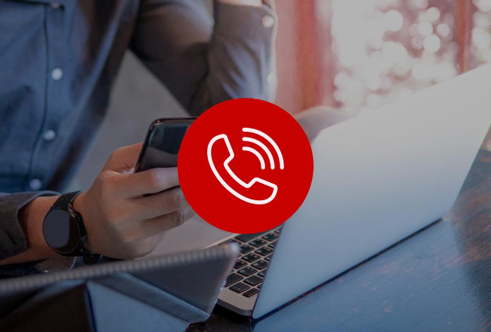 Osoba przy biurku zlaptopem trzyma telefon wdłoni